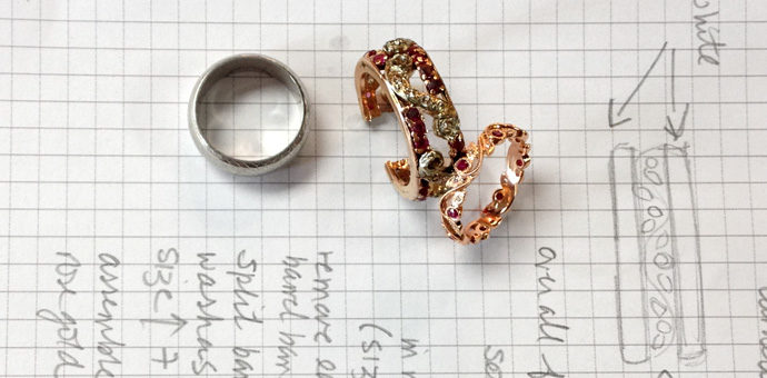 on top of design notes sits white gold band, old anniversary ring, and new ring in progress