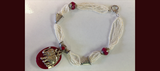 Multi-strand pearls secured with beads and an elephant is the main pendant