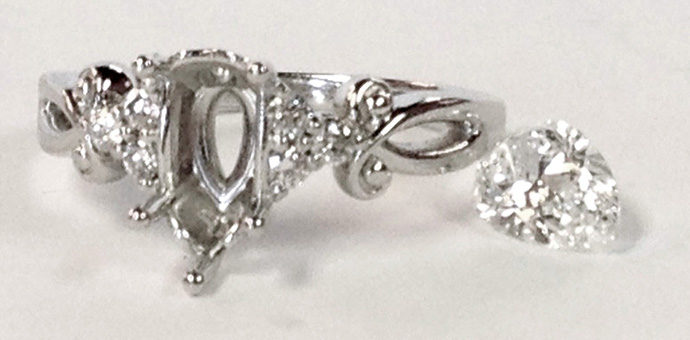 14k white gold ring with a pear shaped center diamond