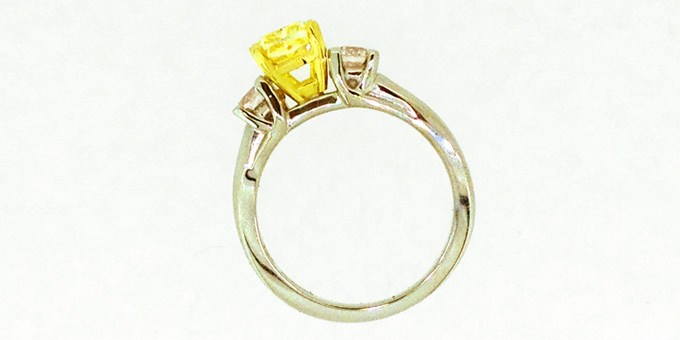 Profile of large yellow and 2 small clear diamond, in gold and platinum setting