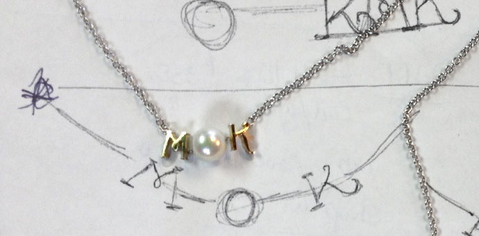 Initials MK, the O is a pearl