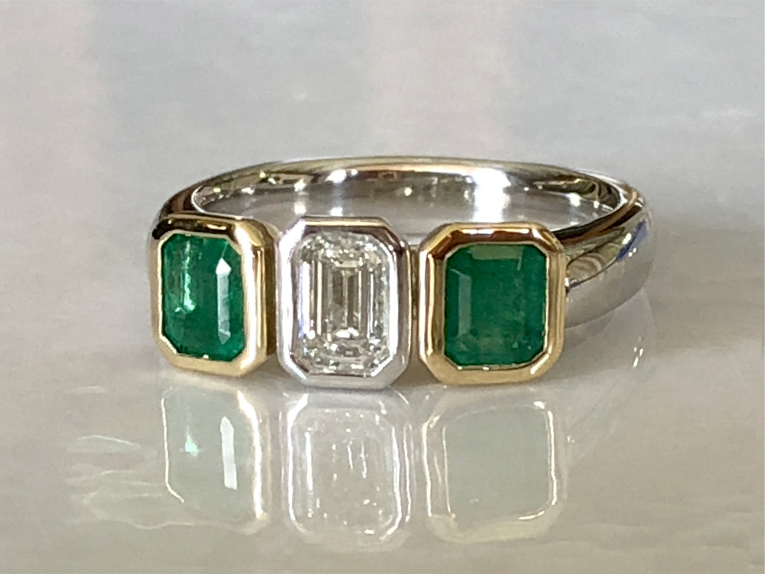 finished ring: emeralds in yellow gold bezels, diamond in platinum