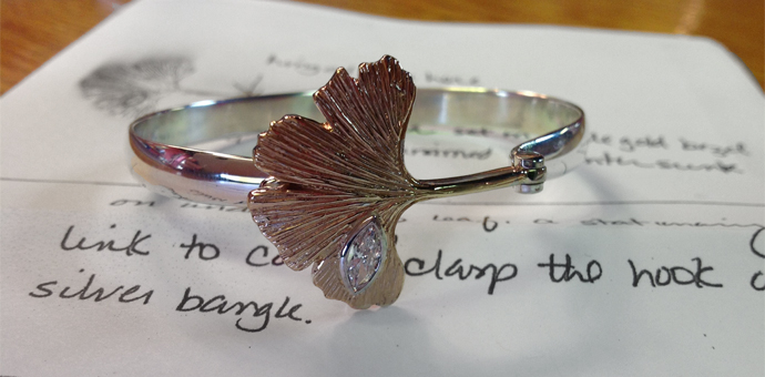 A gold gingko leaf attached to a silver bracelet (bangle) that hinges shut. A beautiful marquis diamond inset.
