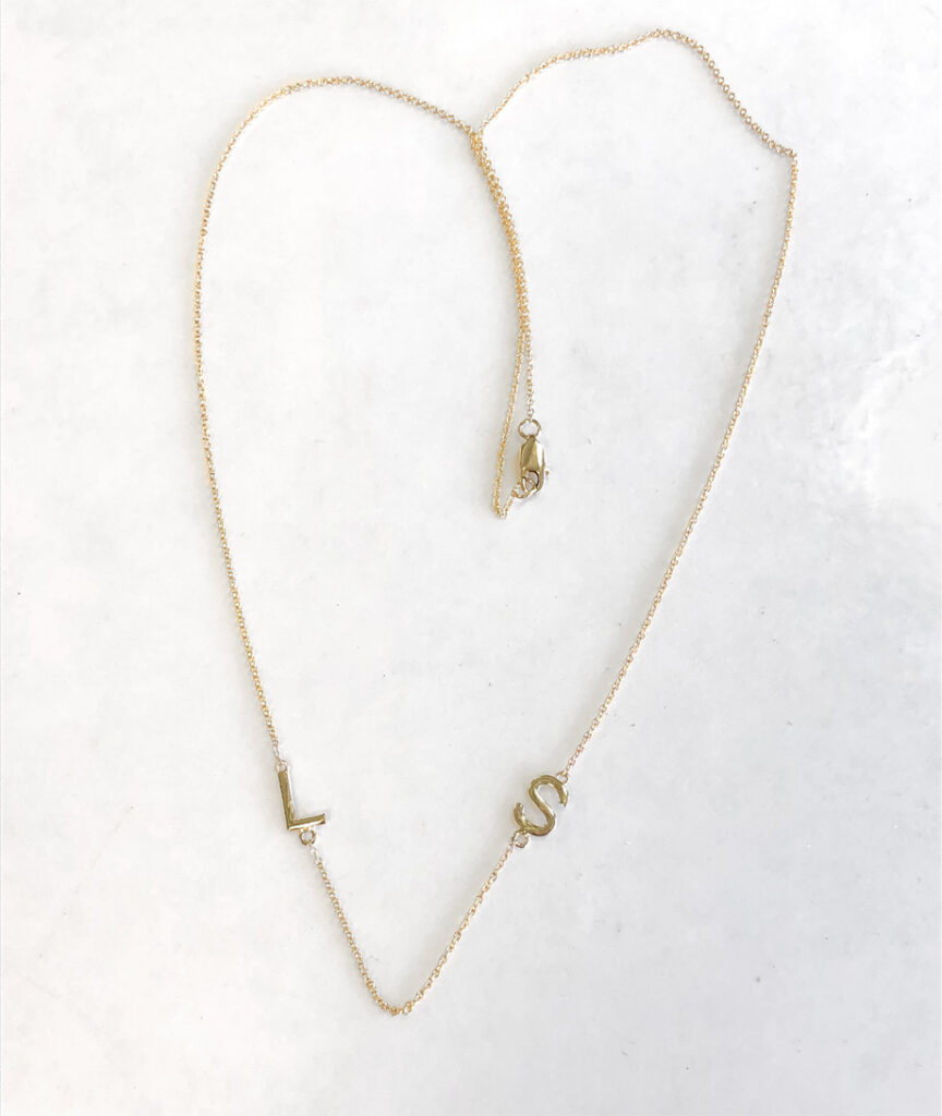 long gold necklace with daughter's initials