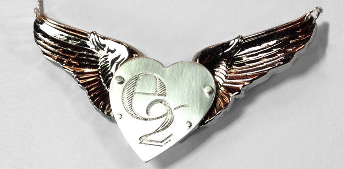 the final pendant - silver heart engraved with e-2, riveted to his squadron wings from first deployment