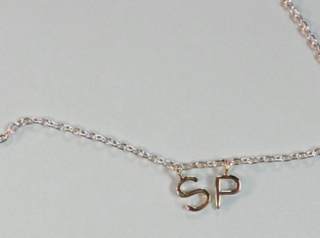 gold initials for each child S and P on a silver necklace