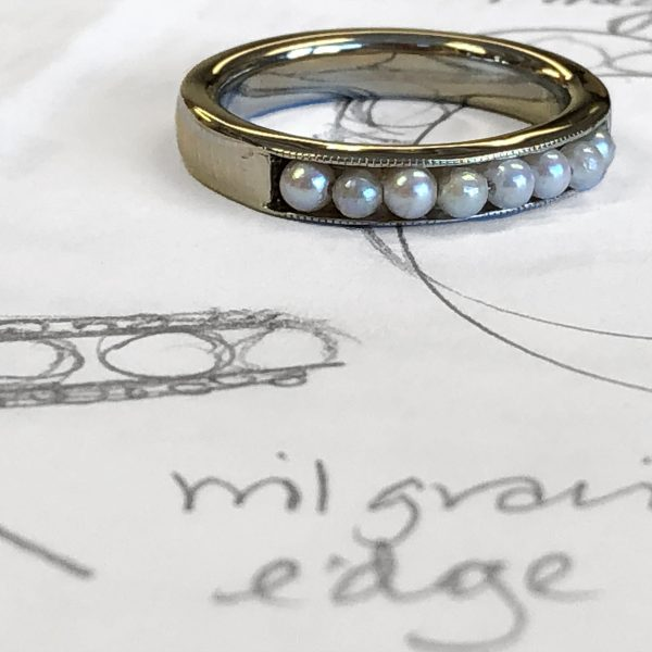 channel ring sitting on top of Raimie's design sketches