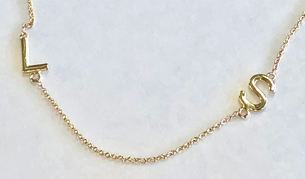 gold initials on mother's necklace (detail)
