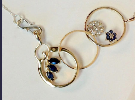 close up of new necklace from old jewelry - 3 linked circles with gems attached