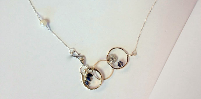 redesigned necklace is 3 rings with interacting gems. pearl in chain too
