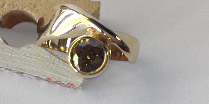 clip holds gold ring with large olive diamond
