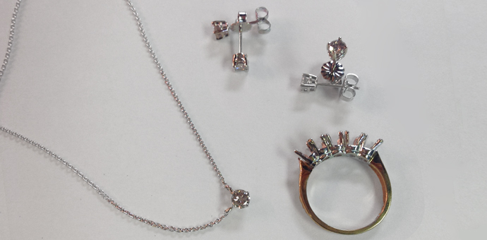 A ring with many prongs is now empty of its diamonds, earrings and necklace for holiday gifts