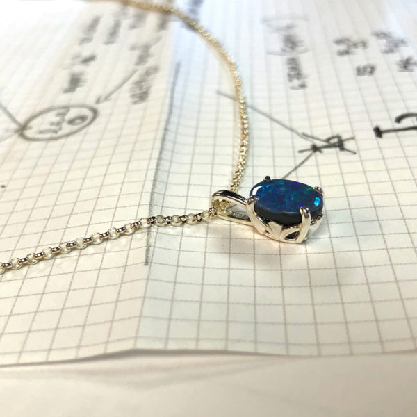 opal necklace on top of design drawings