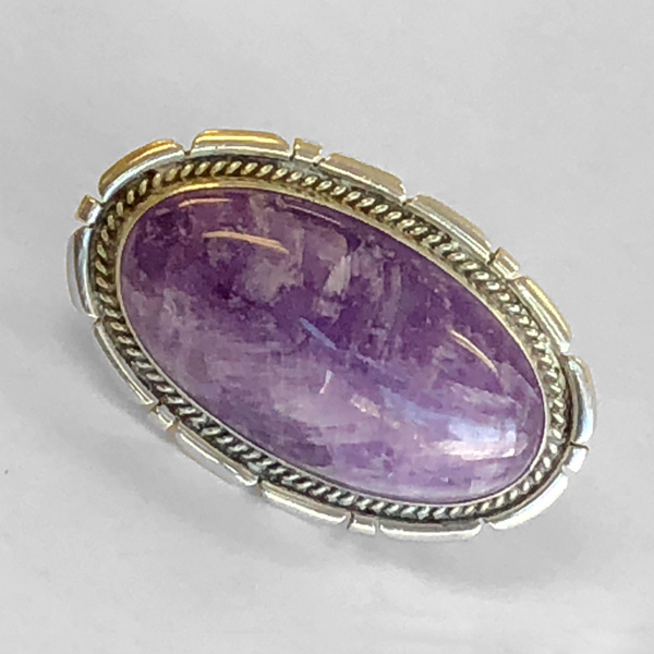 Silver statement ring has large mounting and amethyst