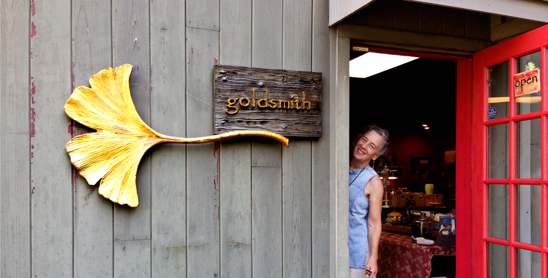 Jeweler Raimie Weber smiling from the shop's door. Goldsmith sign