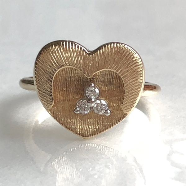 gold heart ring with three small diamonds