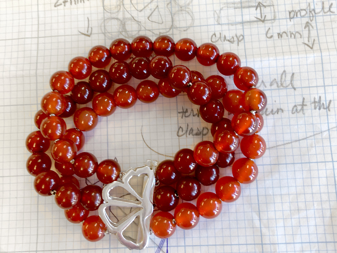 finished redesigned carnelian bead bracelet atop design notes