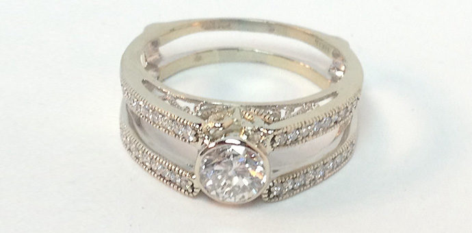 white cold filigree wedding ring with channel diamonds and reused wedding diamond