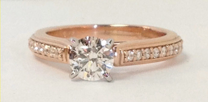 rose gold engagement ring with solitaire diamond, channel diamonds in the band and platinum crown