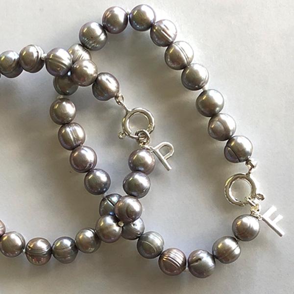 each silver gray pearl bracelet has silver initial