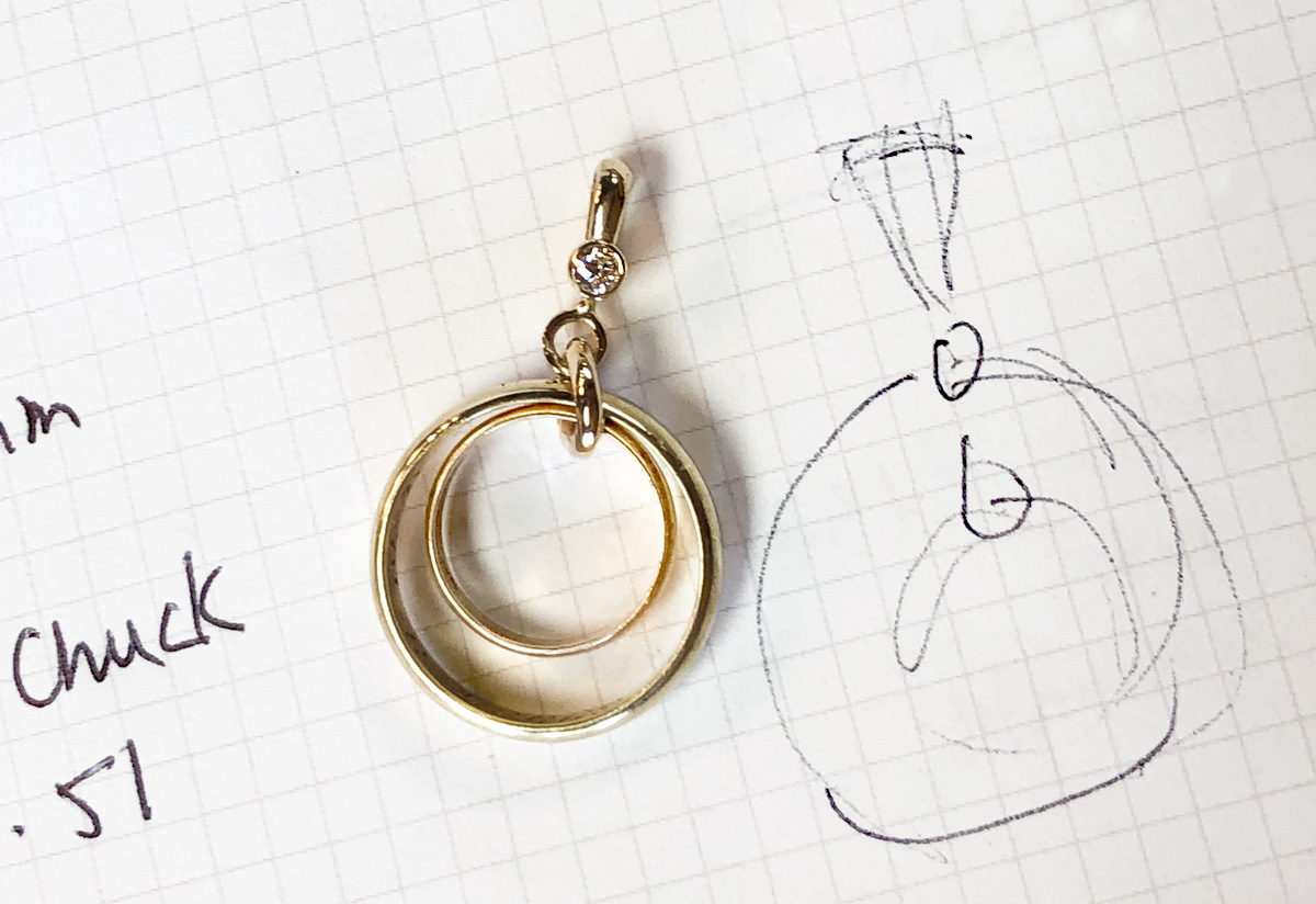 gold talisman pendant made from two family rings