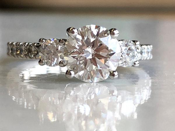 stunning ring has large center diamond, medium side diamonds, several french-set diamonds