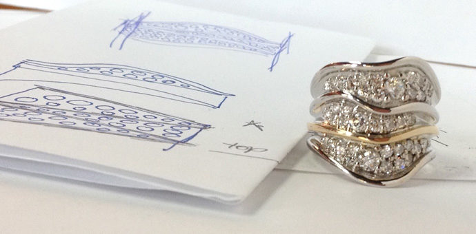 The sketch next to the finished custom ring with many diamonds