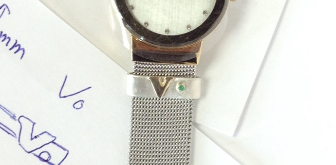 the finished watch band adornment - signature letter and emerald