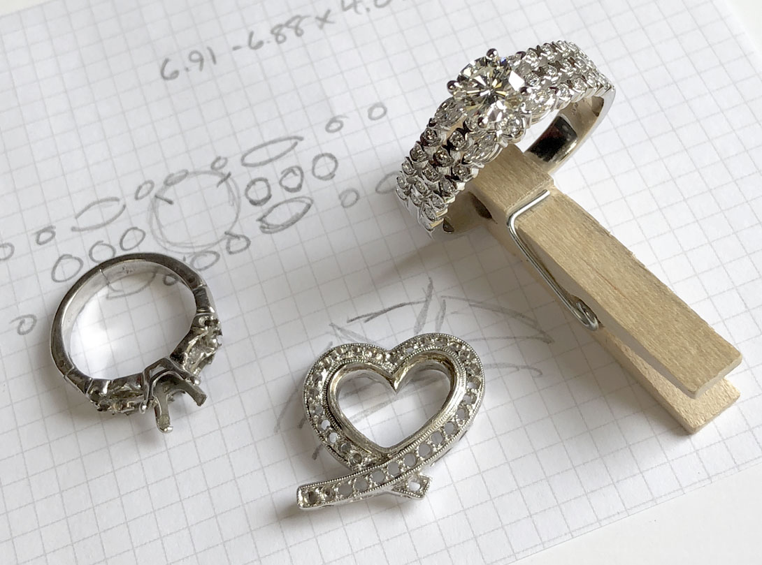 new wedding set next to family heirlooms (ring and heart pendant)