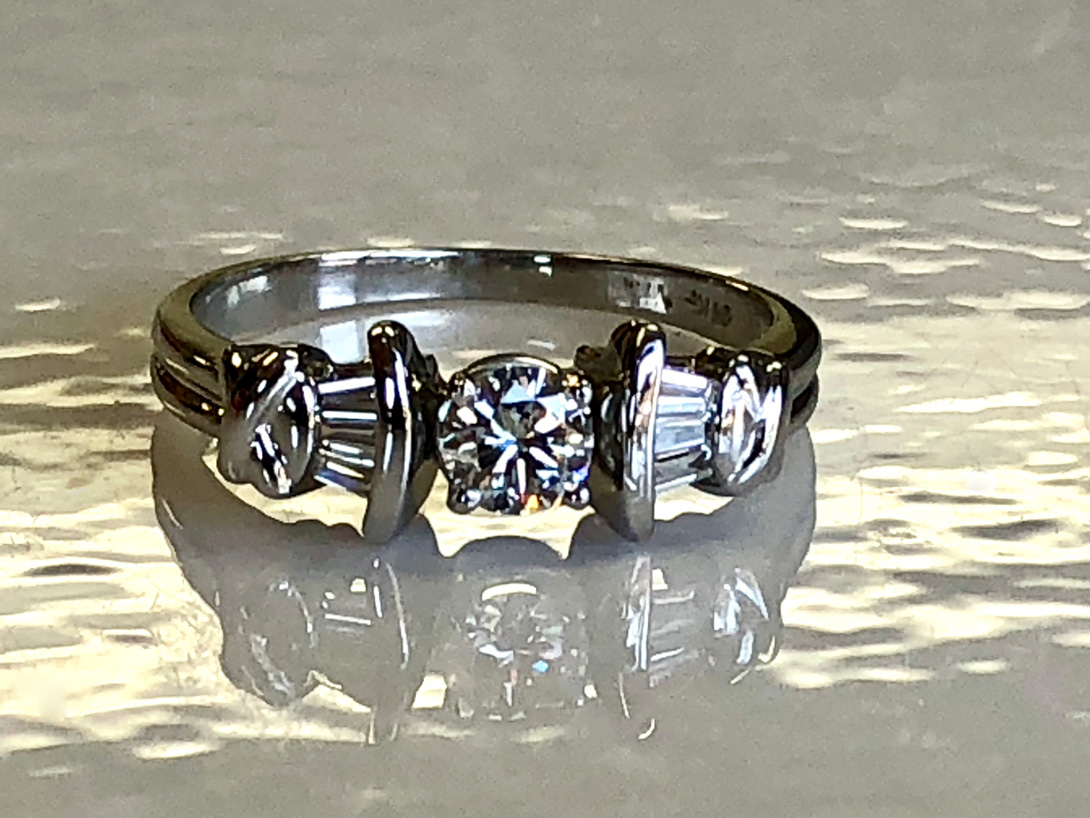white gold ring has side baguettes and center is a round brilliant cut diamond